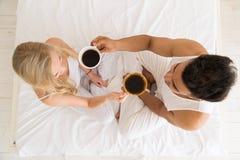 Het jonge Paar drinkt Koffiezitting in Bed, de Gelukkige Glimlach Spaanse Mens en Mening van de Vrouwen de Hoogste Hoek Royalty-vrije Stock Foto's