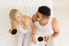 Het jonge Paar drinkt Koffiezitting in Bed, de Gelukkige Glimlach Spaanse Mens en Mening van de Vrouwen de Hoogste Hoek Stock Foto