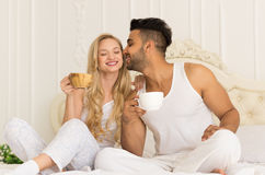 Het jonge Paar drinkt Koffiezitting in Bed, Gelukkige Glimlach Spaanse Man Kussenvrouw royalty-vrije stock fotografie