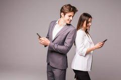 Het jonge paar gebruikt slimme telefoons en glimlacht terwijl status rijtjes op een grijze achtergrond De man bekijkt vrouw Royalty-vrije Stock Foto's