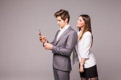 Het jonge paar gebruikt slimme telefoons en glimlacht terwijl status rijtjes op een grijze achtergrond De vrouw bekijkt de mens Stock Afbeeldingen