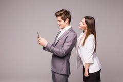 Het jonge paar gebruikt slimme telefoons en glimlacht terwijl status rijtjes op een grijze achtergrond De vrouw bekijkt de mens Stock Foto's