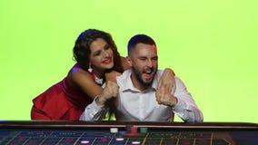 Het jonge paar geniet van overwinning in een spel van roulette stock videobeelden