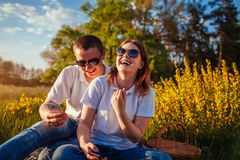 Het jonge paar hangen in hun telefoons en buiten het lachen Vrouw en man het relaing na het hebben van picknick bij zonsondergang royalty-vrije stock fotografie