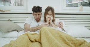 Het jonge paar heeft een griep, leggen zij op het bed onder de deken en voelen te slecht stock footage