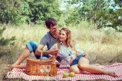 Het jonge paar heeft een rust op picknick, die handen houden Royalty-vrije Stock Afbeeldingen