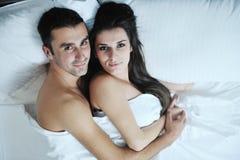 Het jonge paar heeft goede tijd in hun slaapkamer Stock Afbeelding