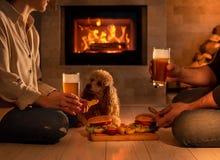 Het jonge paar heeft romantisch diner met hamburgers en bier stock foto