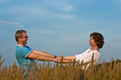 Het jonge paar houdt handen op een weide Stock Foto