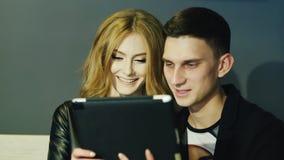 Het jonge paar 20-25 jaar gebruikt de tablet in koffie stock videobeelden