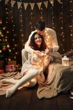 Het jonge paar is in Kerstmislichten en decoratie, gekleed in wit, spar op donkere houten achtergrond, het concept van de de wint stock fotografie