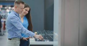 Het jonge paar kiest cooktop in opslag van huishoudapparaten stock footage