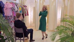 Het jonge paar kiest een kleding voor het meisje in de kleedkamer stock footage