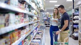 Het jonge paar kiest goederen in supermarkten stock videobeelden