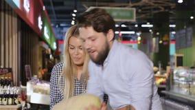Het jonge paar kiest meloen bij de supermarkt stock footage