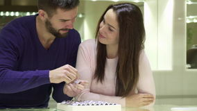 Het jonge paar kiest verlovingsringen bij de juwelenwinkel stock videobeelden