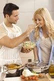 Het jonge paar koken samen in keuken Stock Foto's
