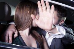 Het jonge paar kussen in auto bij een rode tapijtgebeurtenis, mens beschermt met zijn wapen uitgestrekte blokkerende paparazzifoto Royalty-vrije Stock Foto's