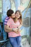 Het jonge paar kussen dichtbij graffitiachtergrond. Stock Fotografie