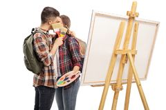 Het jonge paar kussen naast een canvas en het verbergen van hun gezichten met penselen stock foto's