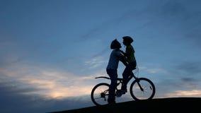Het jonge paar kussen op fiets bij zonsondergang stock videobeelden