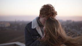 Het jonge paar kussen op hemelcityscape achtergrond, de jeugdliefde, samenhorigheid Romantische datum op het hoge dak stock footage
