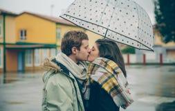 Het jonge paar kussen in openlucht onder paraplu in een regenachtige dag Stock Afbeeldingen