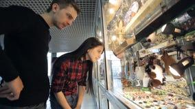 Het jonge paar let op herinneringen in luchthavenwinkel stock videobeelden