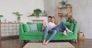 Het jonge paar let op TV toont samen en lachend stock footage