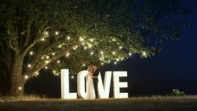 Het jonge paar in liefde in avondjurken danst dichtbij liefde lichte brieven stock afbeeldingen