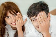 Het jonge paar in liefde die samen op wit bed liggen en toont de Romantische Verhouding van de trouwringverjaardag stock foto's