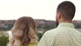 Het jonge paar in liefde geniet van het warme weer en van de mening van stad in de zomerpark stock videobeelden