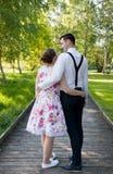 Het jonge paar in liefde omhelst Lange houten weg Stock Afbeelding