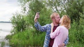Het jonge paar in liefde op de achtergrond van de rivier neemt een selfie op de telefoon een vrouw en een man bevinden zich tegen stock footage