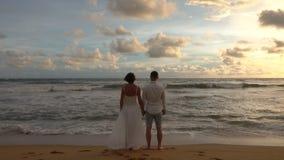 Het jonge paar in liefde op een romantische datum ontmoet de zonsondergang die op het strand, handen houden stock videobeelden