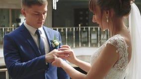 Het jonge paar in liefdejonggehuwden ruilt gouden trouwringen stock video