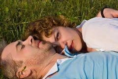 Het jonge paar ligt op een gras Stock Afbeelding