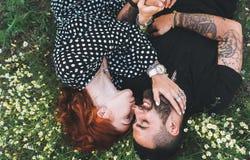 Het jonge paar ligt op het gebied met madeliefjes royalty-vrije stock afbeelding