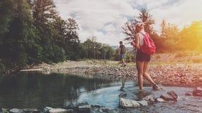 Het jonge paar loopt langs de bank van een bergrivier in de zomer Een meisje met een bobcat kruist de rivier want, tegen a waad stock fotografie