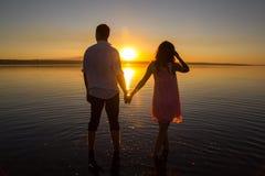 Het jonge paar loopt in het water op de zomerstrand Zonsondergang over het overzees Twee silhouetten tegen de zon Enkel echtpaar royalty-vrije stock foto