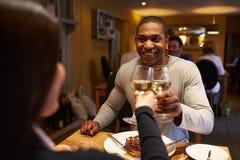 Het jonge paar maakt een toost bij restaurant, over--schoudermening royalty-vrije stock fotografie