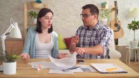 Het jonge paar maakt terwijl thuis het maken van berekeningen van documenten met een calculator ruzie stock videobeelden