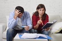 Het jonge paar maakte zich en wanhopig thuis op geldproblemen in de bankbetalingen van de spanningsboekhouding ongerust stock afbeelding