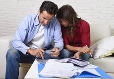Het jonge paar maakte zich en wanhopig thuis op geldproblemen in de bankbetalingen van de spanningsboekhouding ongerust royalty-vrije stock afbeeldingen