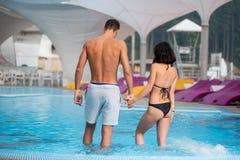 Het jonge paar met perfect cijfer die zich in het zwembad bevinden en houdend handen op luxe neemt zijn toevlucht Achter mening Royalty-vrije Stock Fotografie