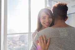 Het jonge Paar omhelst Moderne Overzeese van het Flat Grote Panoramische Venster Mening, de Mens van het Mengelingsras en Vrouwen stock foto's