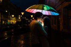 Het jonge paar onder een paraplu kust bij nacht op een stadsstraat Stock Afbeelding