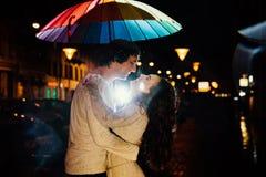 Het jonge paar onder een paraplu kust bij nacht op een stadsstraat Stock Afbeeldingen