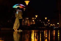 Het jonge paar onder een paraplu kust bij nacht op een stadsstraat Stock Foto