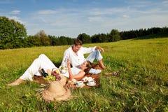 Het jonge paar ontspannen in aard die picknick heeft Stock Foto's